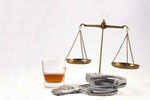 handcuffs next to a toy car, alcoholic drink and scale of justice, DWI lawyer