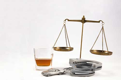 alcoholic drink next to scale of justice and handcuffs with white background