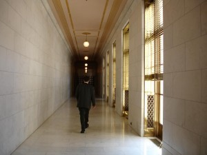 lawyer walking down an empty hallway in building