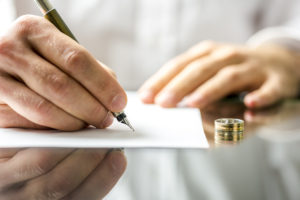 a person signing divorce papers