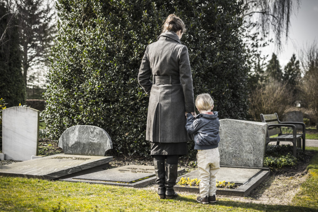mother and child grieving at a graveyard