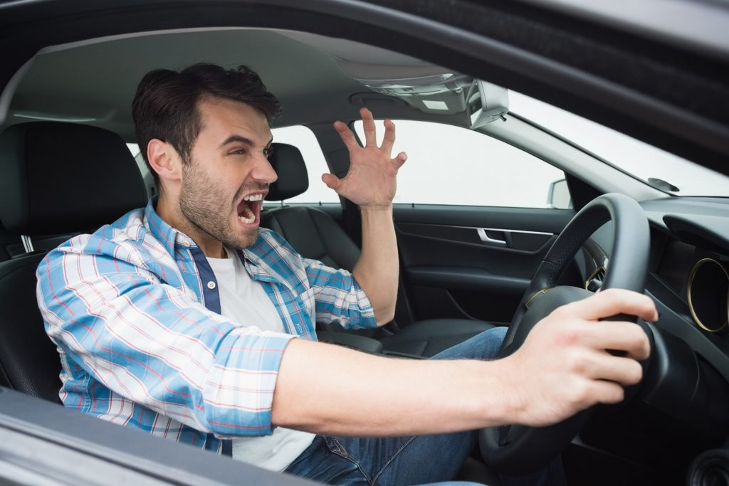 young man experiencing road rage in danger of getting into a car accident