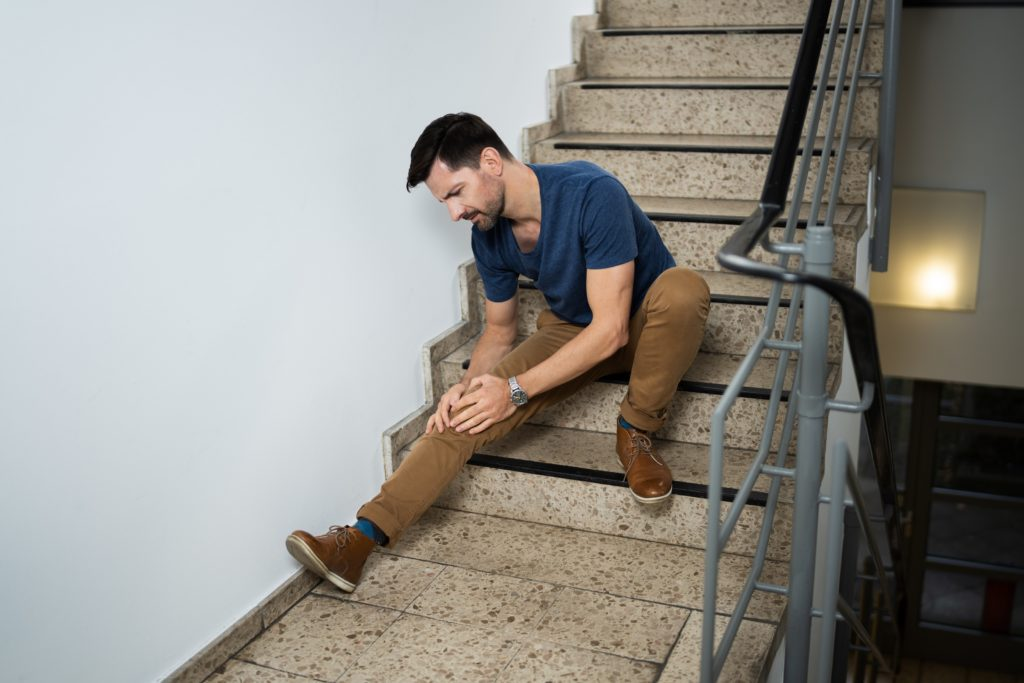 Man Sitting On Staircase After Slip And Fall Accident