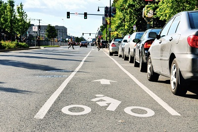 Still of a bike lane on the right side of a street taken in the middle of the day, broad daylight.