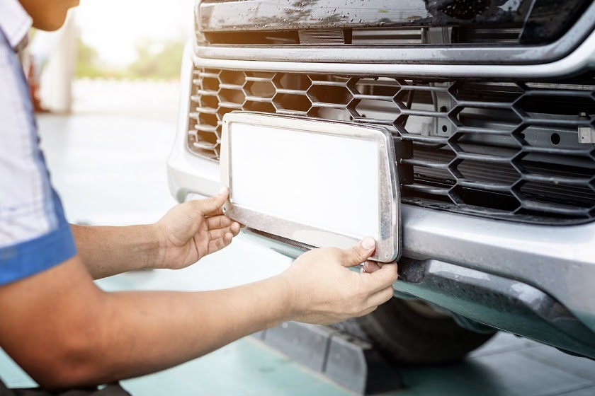 Car technician changes out the license plates of a truck at a vehicle service center.