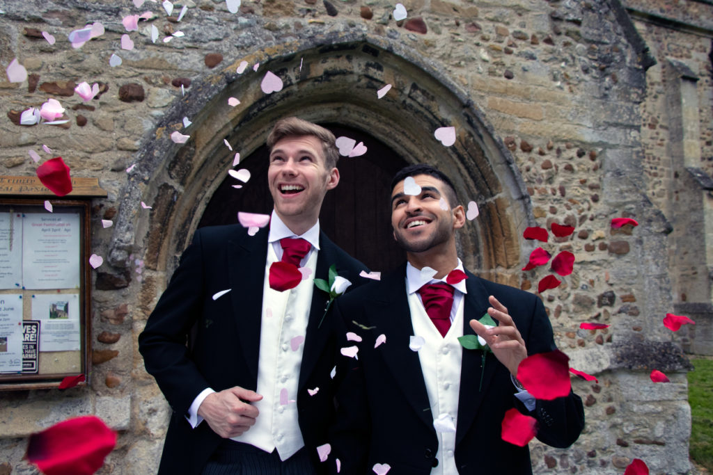 Two young men walking out from a church after their marriage with flower petals being thrown on them by happy bystanders
