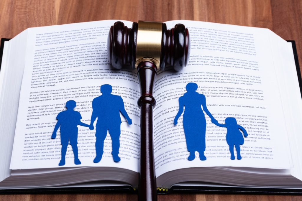 family law represented with a split family over a law book and gravel